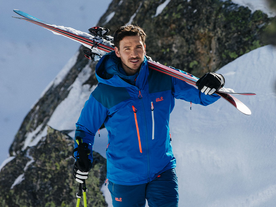 Man wearing skiwear and carrying skis over his shoulders
